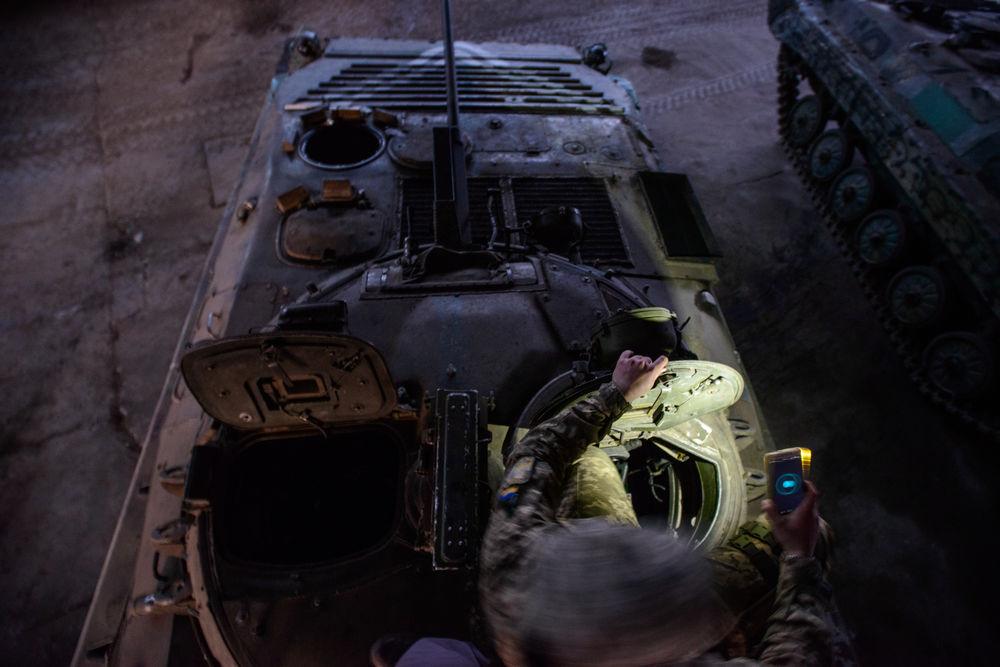solider climbing into a tank - photo by garrett n