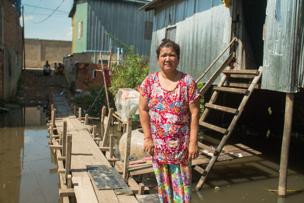 Srey Sina, who learned about Jesus from OM MTI, stands in front of her house in a slum in Cambodia. Photo by Jay Schipper.