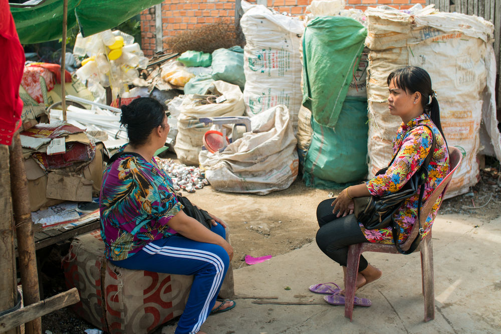 Mom Som, right, talks to a woman in a Cambodian slum as part of her work for OM MTI.